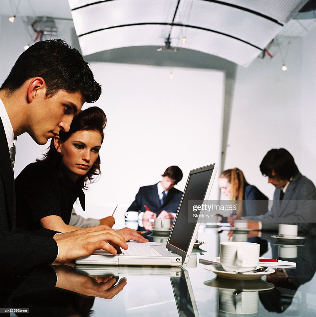 view of a young man and woman working on a laptop : Stock Photo