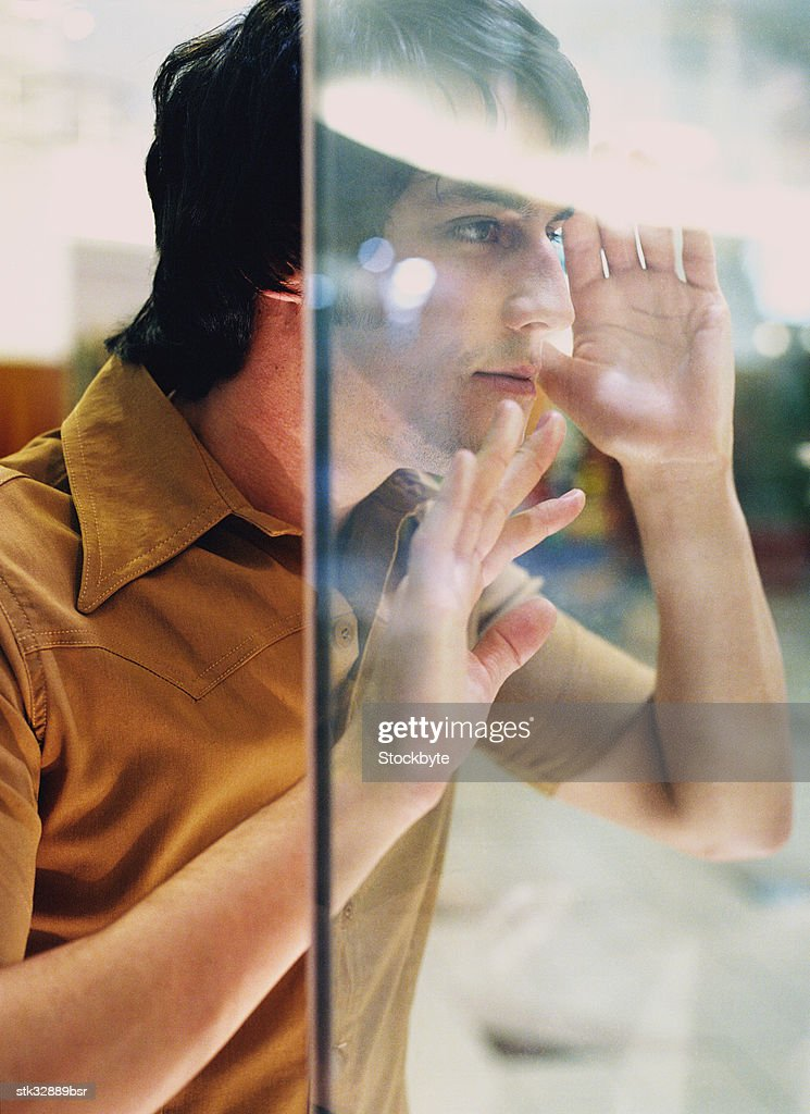 view of a young man looking through a display window
