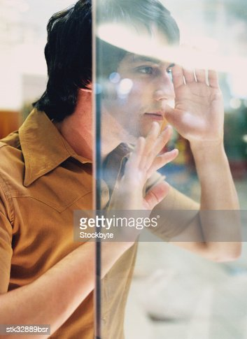 view of a young man looking through a display window : Stock Photo