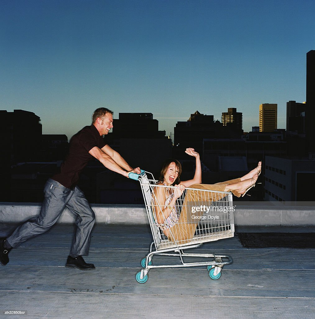 view of a young man pushing a young woman in a shopping cart : Stock Photo