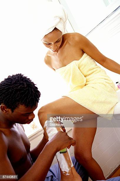 view of a young man shaving a young woman's legs
