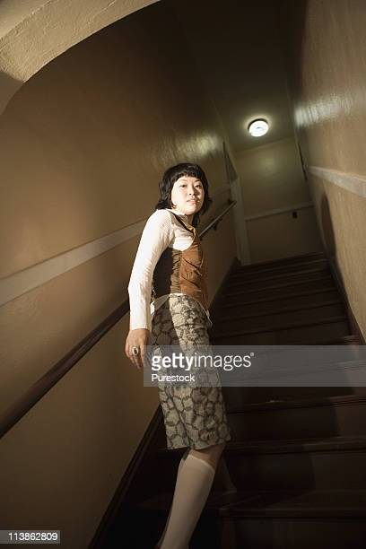 View of a young woman at bottom of staircase