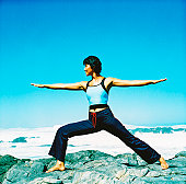 view of a young woman doing yoga at the beach