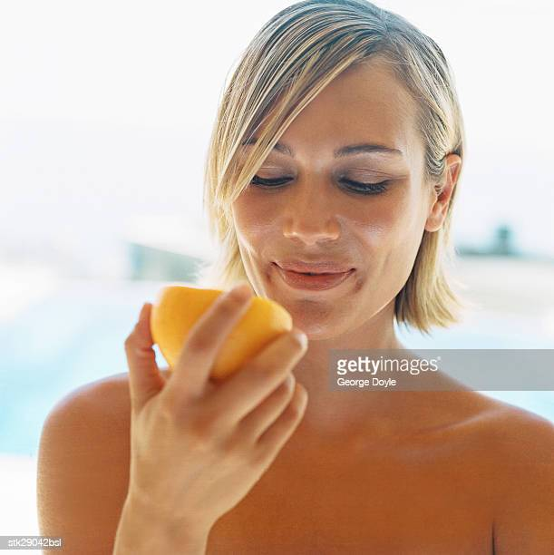 view of a young woman eating a grapefruit