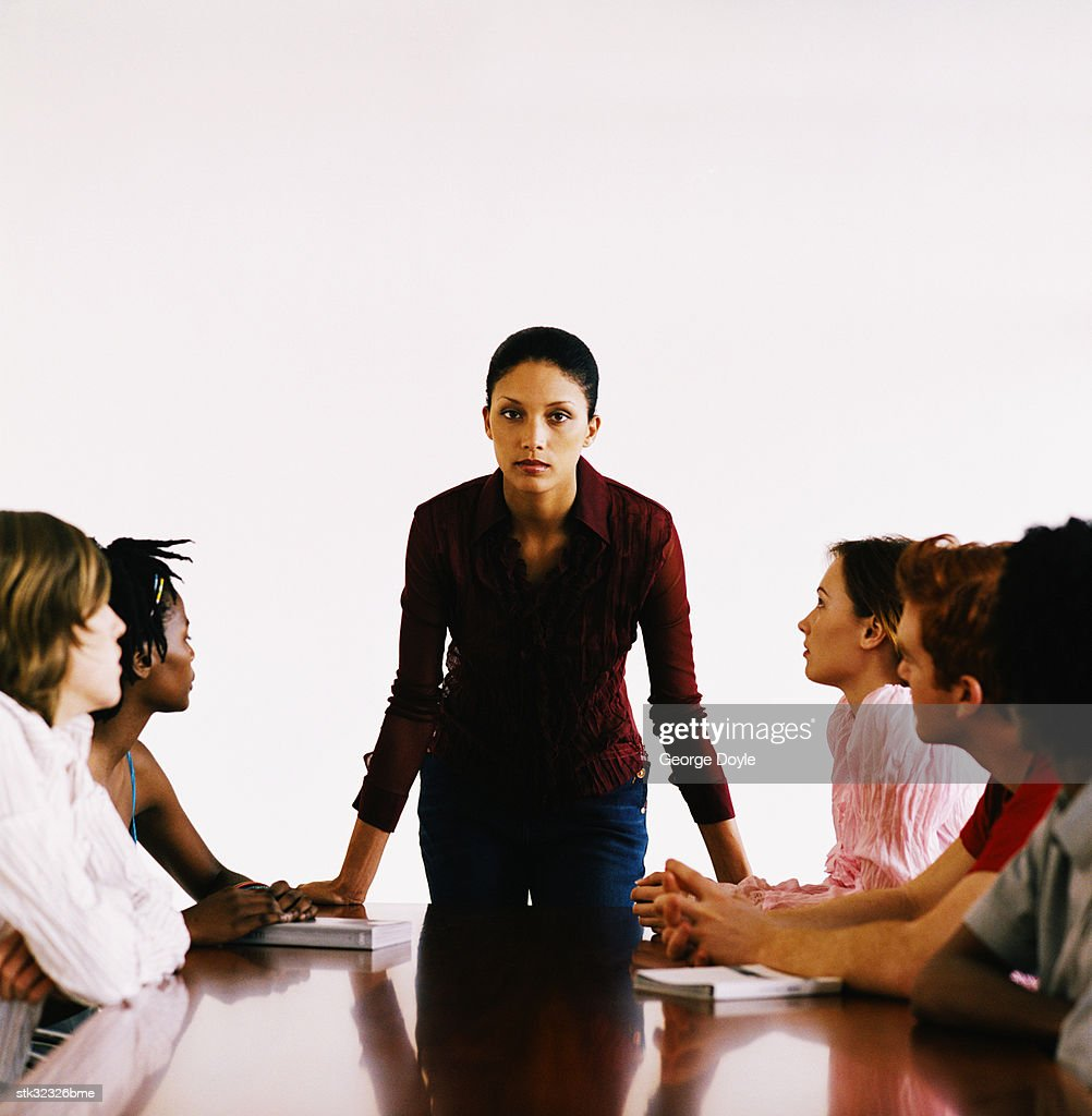 view of a young woman standing and a group of people seated at the table : Stock Photo