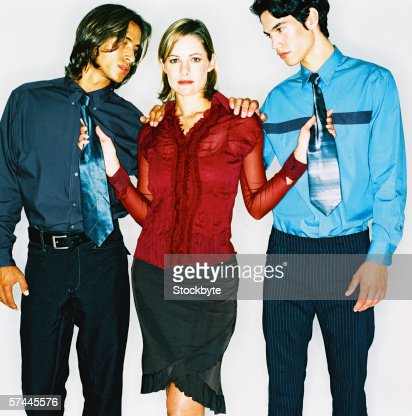 view of a young woman standing between two men and pulling them towards her with their neckties : Stock Photo