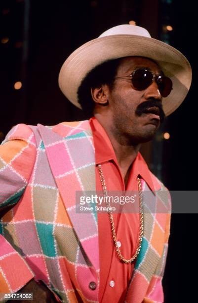 View of American actor and comedian Bill Cosby in costume and with a cigarette in his mouth New York New York 1970s He wears a straw hat sunglasses...