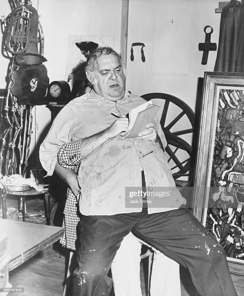 View of American actor and comedian <a gi-track='captionPersonalityLinkClicked' href=/galleries/search?phrase=Zero+Mostel&family=editorial&specificpeople=207033 ng-click='$event.stopPropagation()'>Zero Mostel</a> (1915 - 1977) as he sits on the lap of an unidentified person, whose arms wrap around Mostel and write on a notepad, New York, New York, 1971.