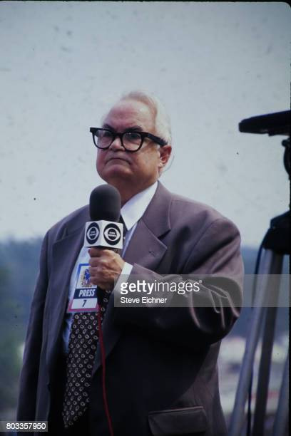 View of American actor Calvert DeForest in costume as charcter Larry 'Bud' Melman as he holds a CBS News microphone at the Woodstock '94 festival...