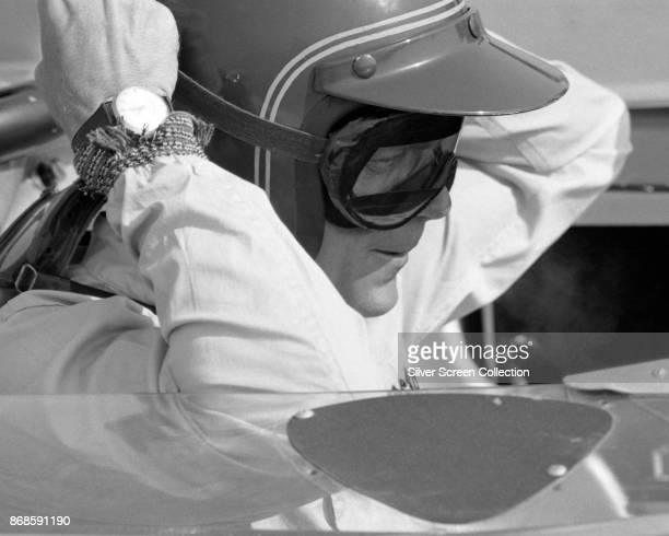 View of American actor Steve McQueen in Firestone racing suit adjusts his goggles as he sits in a car at Riverside Raceway Riverside California July...
