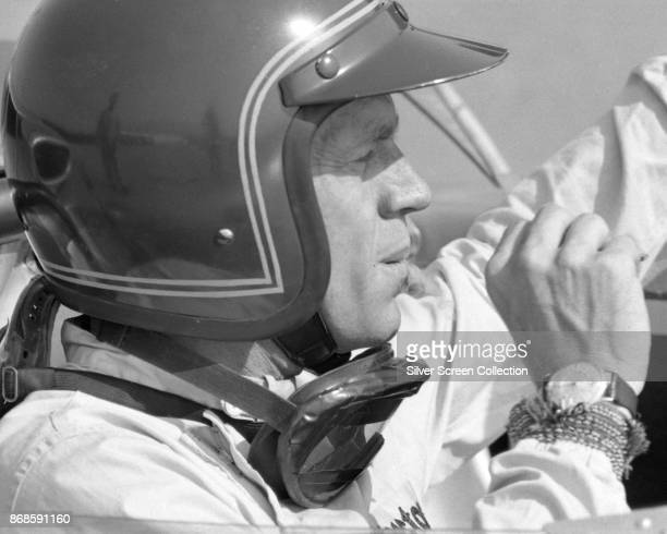 View of American actor Steve McQueen in Firestone racing suit as he sits in a car at Riverside Raceway Riverside California July 1966