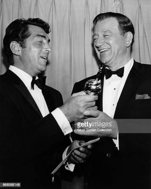 View of American actors Dean Martin and John Wayne as they share a laugh over Martin's 'Best TV Star Male' trophy at the 24th Annual Golden Globe...