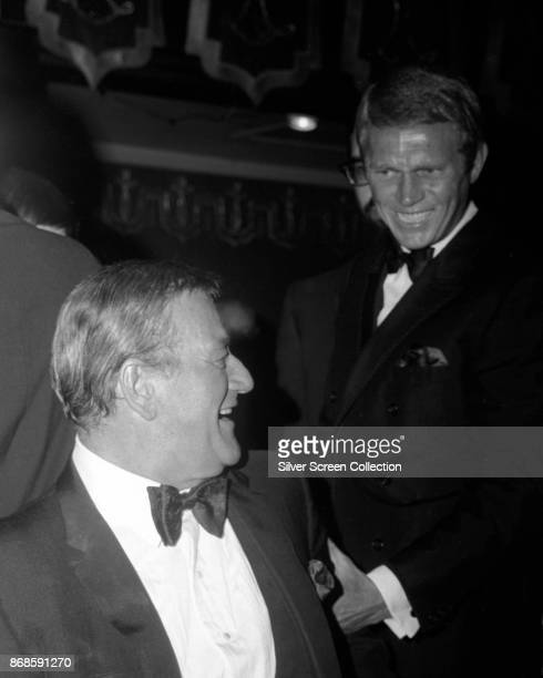 View of American actors John Wayne and Steve McQueen as they greet one another at an unspecified event 1960s or 1970s