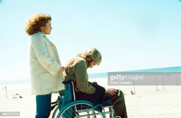 View of American actress Jane Fonda stands behind fellow actor Jon Voight in a wheelchair on a beach in a scene from the movie 'Coming Home'...