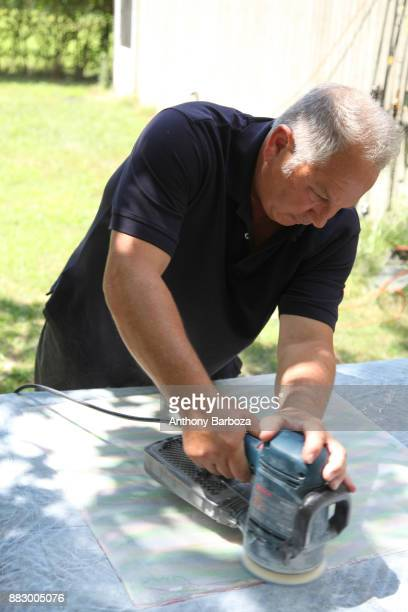 View of American artist Mike Solomon as he uses an electric sander outside his Long Island studio East Hampton New York August 10 2011
