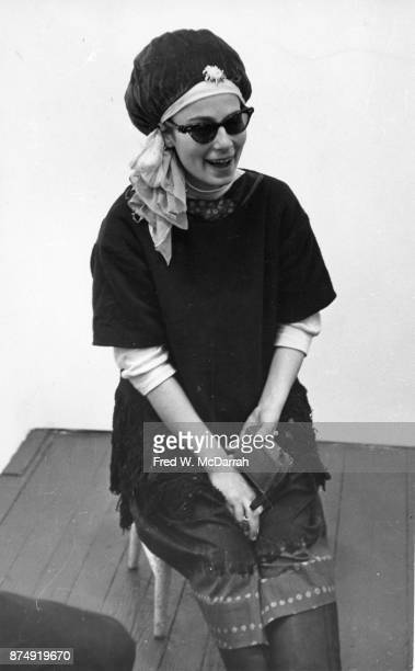 View of American film director and performance artist Barbara Rubin as she sits on a stool in a corner of Allen Ginsberg's apartment New York New...