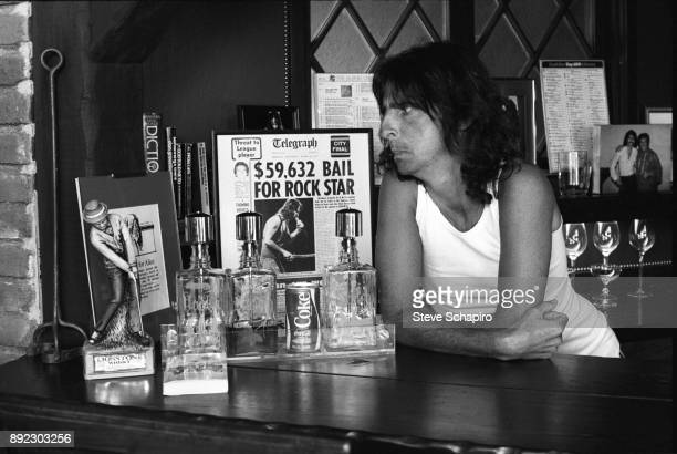 View of American musician Alice Cooper as he leans on a counter Los Angeles California 1978 Next to him is a framed newspaper headline that reads...