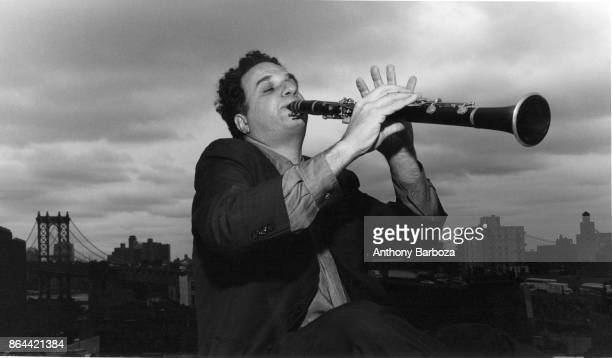 View of American musician David Krakauer as he plays clarinet on a rooftop New York New York 1990s