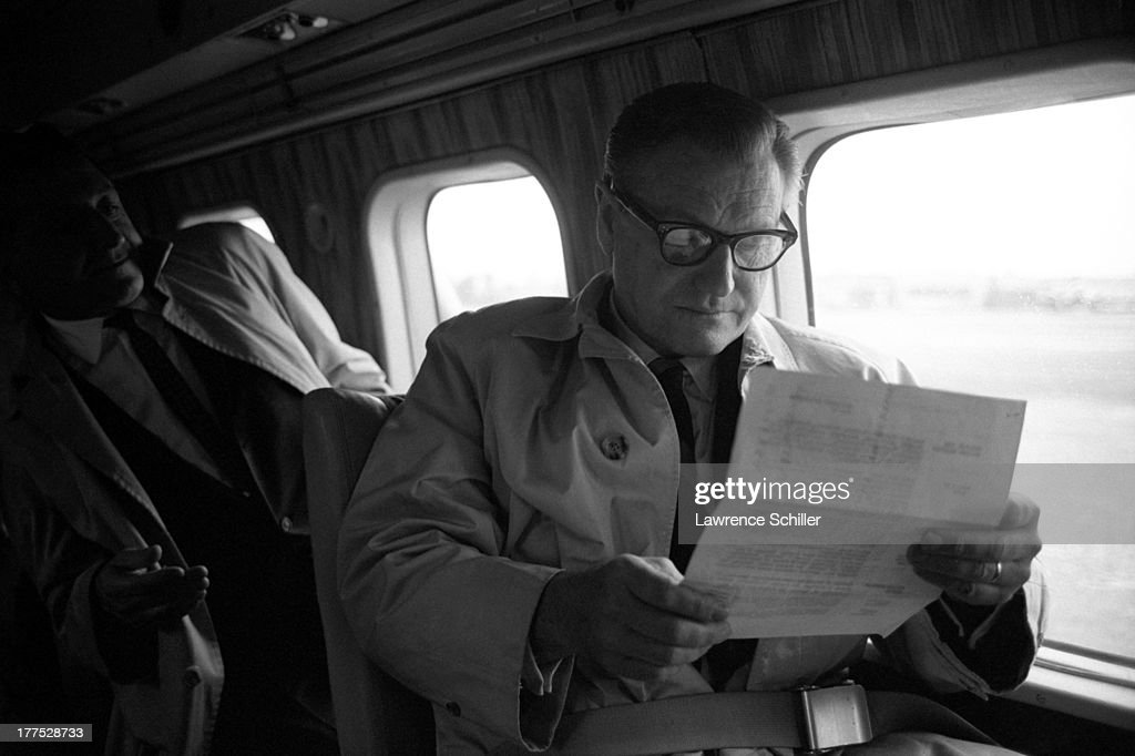 View of American politician Nelson Rockefeller (1908 - 1979) reads a document on a plane as he campaigns for the Republican presidential nomination, California, 1964.