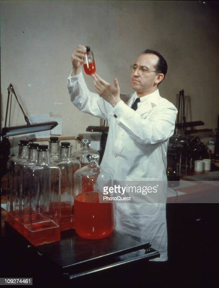 View of American scientist and physician Jonas Salk developer of the polio vaccine wearing a white lab coat and smiling while holding up a bottle in...