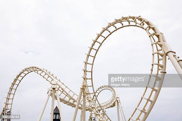 View of amusement park rollercoaster against grey sky