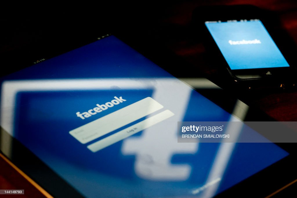A view of an Apple iPad and iPhone displaying the Facebook app's splash screen May 10, 2012 in Washington, DC. Social-networking giant Facebook will go public on the NASDAQ May 18 with its initial public offering, trading under the symbol FB, in an effort to raise $10.6 billion. AFP PHOTO / Brendan SMIALOWSKI