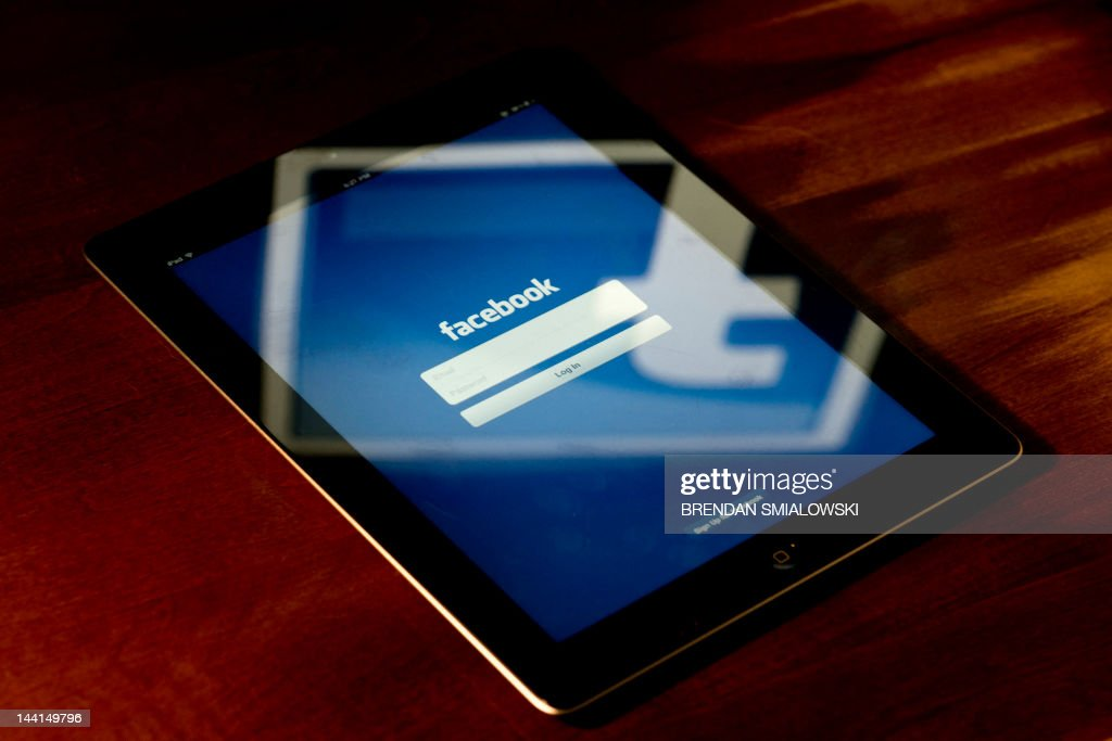 A view of an Apple iPad displaying the Facebook app's splash screen May 10, 2012 in Washington, DC. Social-networking giant Facebook will go public on the NASDAQ May 18 with its initial public offering, trading under the symbol FB, in an effort to raise $10.6 billion. AFP PHOTO / Brendan SMIALOWSKI