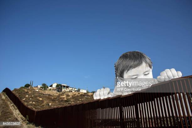 TOPSHOT View of an artwork by French artist JR on the USMexico border in Tecate California United States on September 6 / AFP PHOTO / GUILLERMO ARIAS