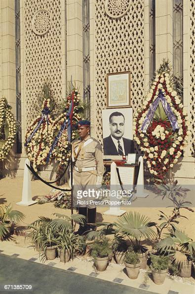 View of an Egyptian soldier guarding the tomb of President Gamal Abdel Nasser of Egypt with large wreaths of flowers and palm fronds surrounding the...