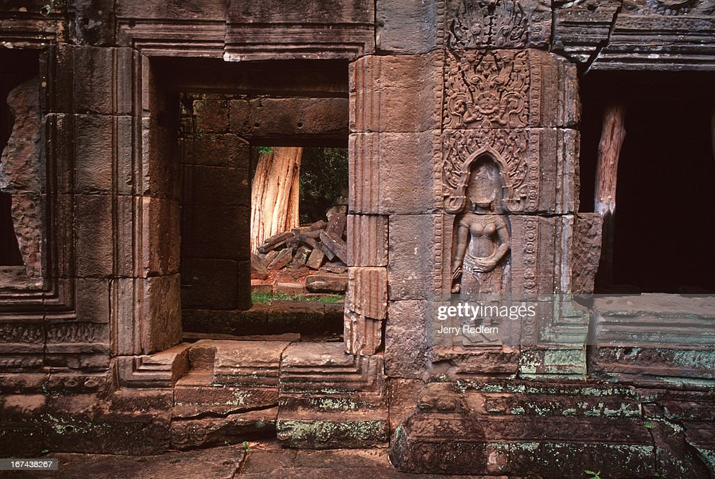 View of an interior courtyard with an Apsara (mythical Hindu celestial dancer) with a missing head, chipped away by looters in the Preah Khan temple in the ancient Angkor temple complex..