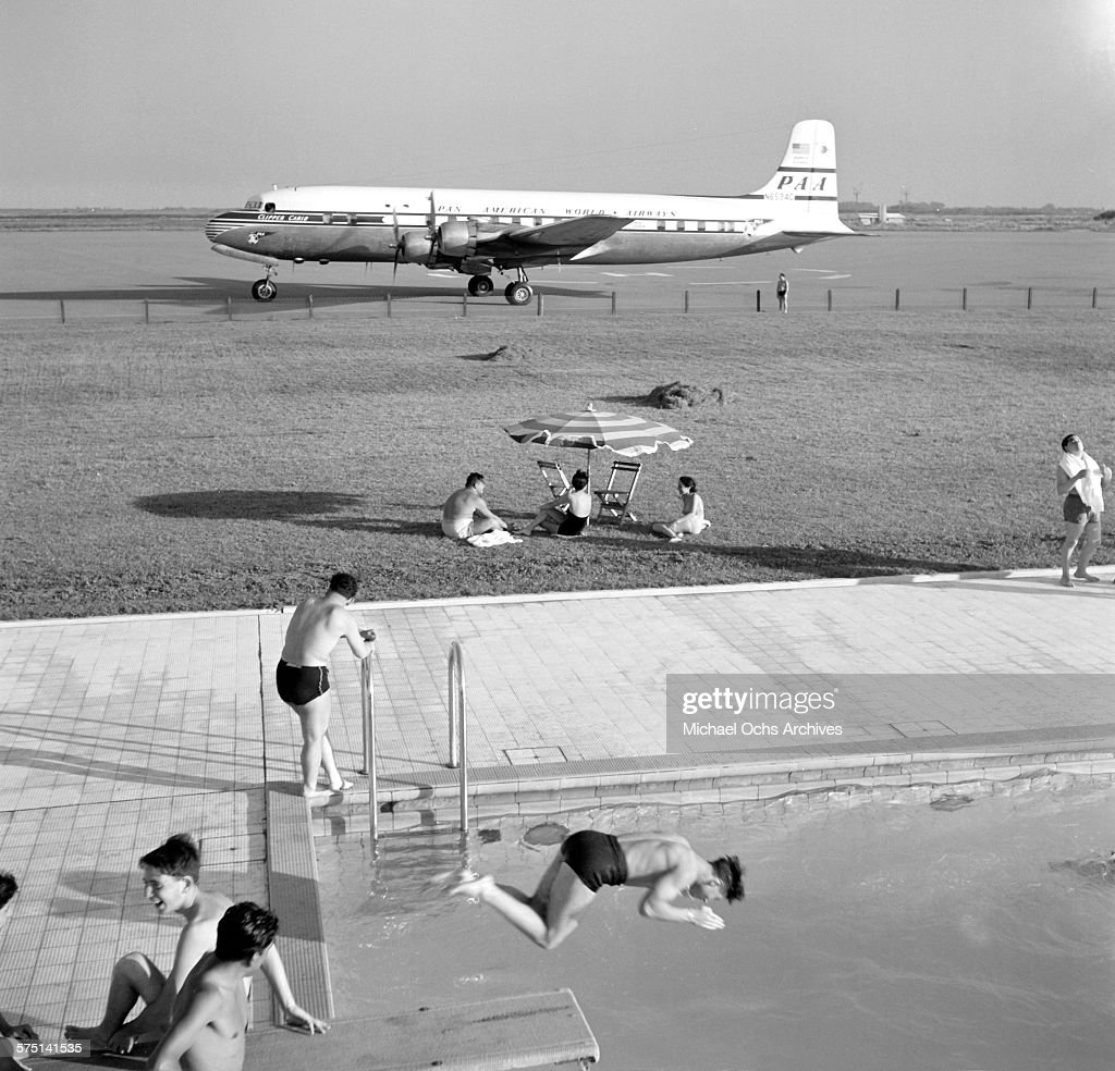 A view of an Pan American Airways DC-4 Clipper airplane on the tarmac as people swim in a swimming pool at the Ezeiza Airport in Buenos Aires, Argentina.