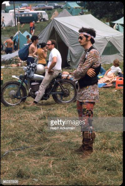 View of an unidentified festival goer as he stands arms crossed and watches a performace during the Woodstock Music and Arts Fair Bethel New York...