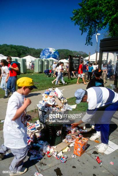 View of an unidentified man and a pair of boys as they add trash to an overflowing garbage can during an Earth Day rally Washington DC April 22 1990