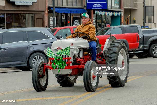 View of an unidentified man as he drives a restored midcentury Ford '8n' tractor during the the annual Saint Patrick's Day Parade Emporia Kansas...