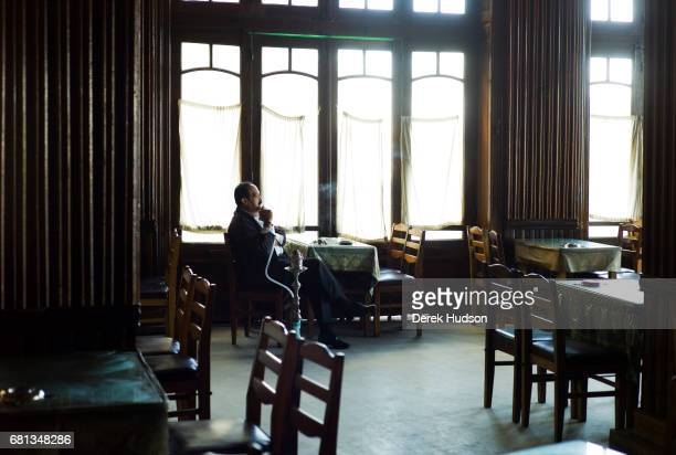 View of an unidentified man as he smokes a water pipe as he sits apparently alone in a cafe Alexandria Egypt December 11 2009