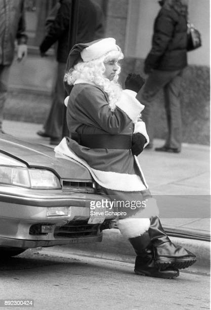 View of an unidentified man in a Santa Claus costume as he leans on the hood of a parked car Chicago Illinois 2014