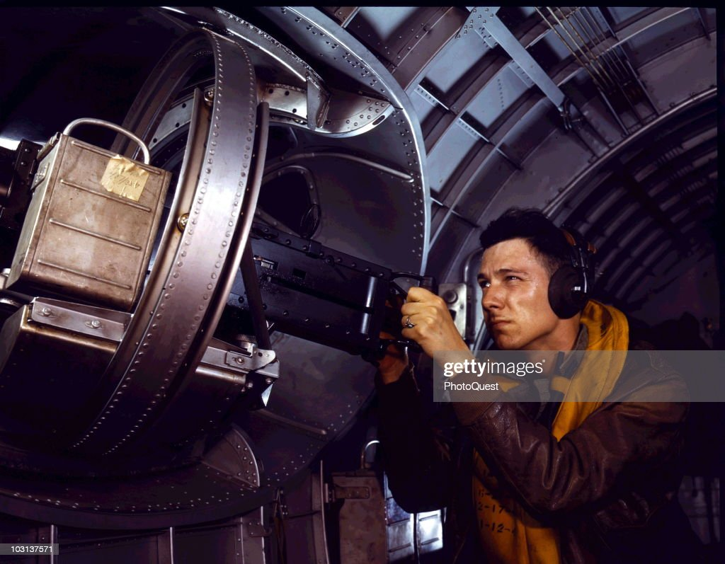 View of an unidentified soldier as he peers along the site of one of machine guns in a B-17 bomber, May 1942. The original caption reads 'Hitler would like this man to go home and forget about the war. A good American non-com at the side machine gun of a YB-17 bomber is a man who knows his business and works hard at it.' The YB-17 (or Y1-B17) was a prototype version of the B-17 production model.