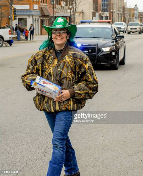 View of an unidentified woman in a camouflage jacket and a green sequinned cowboy hat decorated with shamrock designs as she marches in the annual...