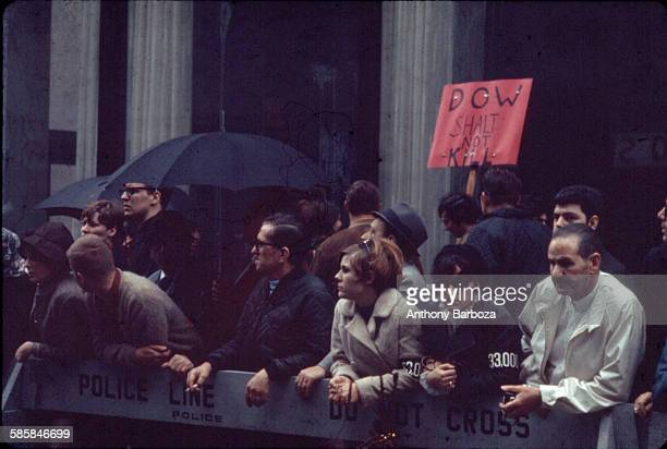View of antiVietnam war protestors as they stand behind a police barrier New York 1960s One is holding up a sign that reads 'Dow Shalt Not Kill'