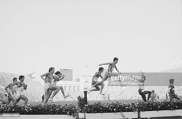 View of athletes clearing the water jump hazard during competition in the Men's 3000 metres steeplechase event with Roger Hackney of Great Britain...