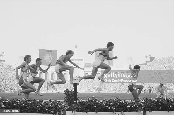 View of athletes clearing the water jump hazard during competition in the Men's 3000 metres steeplechase event at the 1984 Summer Olympics inside the...