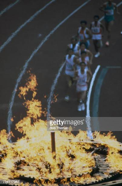View of athletes competing in the final of the Men's 5000 metres event as they run past the cauldron flame inside the Olympic stadium in Seoul South...