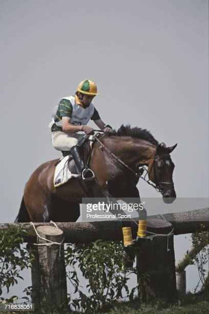 View of Australian equestrian Matthew Ryan riding Kibah Tic Toc negotiating a wooden hazard and grass slope during competition in the cross country...