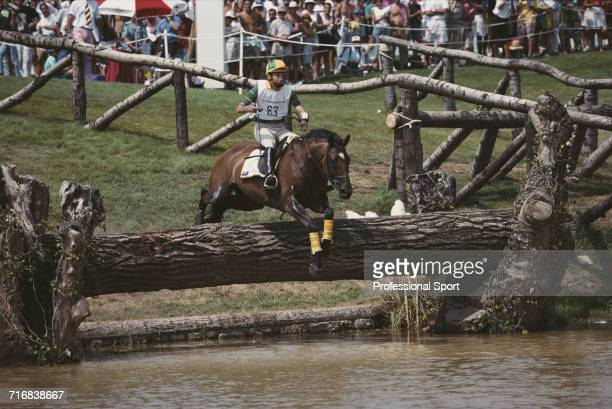 View of Australian equestrian Matthew Ryan riding Kibah Tic Toc negotiating a wooden log hazard in to water during competition in the cross country...