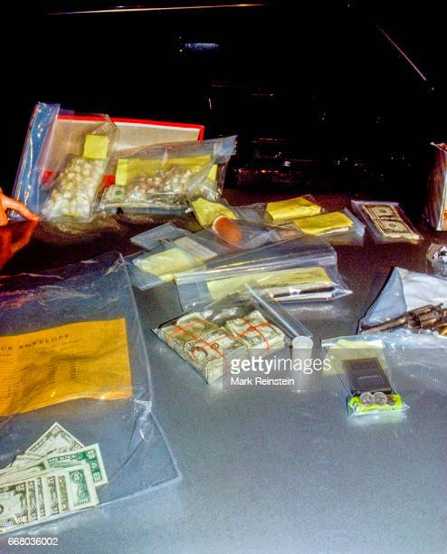 View of bags of drugs money a gun and other items displayed on the hood of a car following their seizure in a Prince Georges County Police task force...