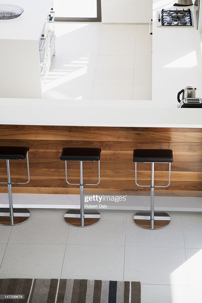 View of barstools below counter of modern kitchen : Stock Photo