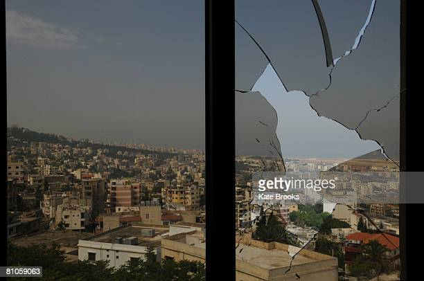 A view of Beirut is seen through the broken window of a building damaged during sectarian clashes on May 12 2008 in Shweifat near Beirut Lebanon...
