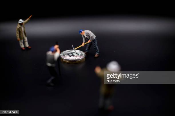 A view of Bitcoin token and a miner miniature figures