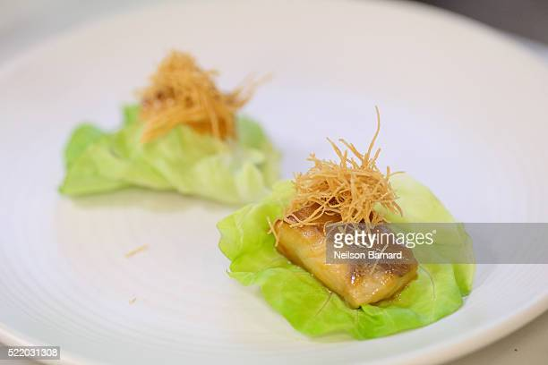 View of black cod on butter lettuce finished dish during Chefs Taku Sato and Ricky Estrellado's Nobu Classics class at The 8th Annual New York...