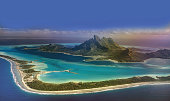High angle view of beautiful Bora Bora island, a gem in the French Polynesian islands, as seen from airplane window during landing.